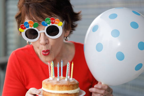 woman-with-happy-birthday-glasses-blowing-out-candles-on-a-birthday-picture-id1165027849